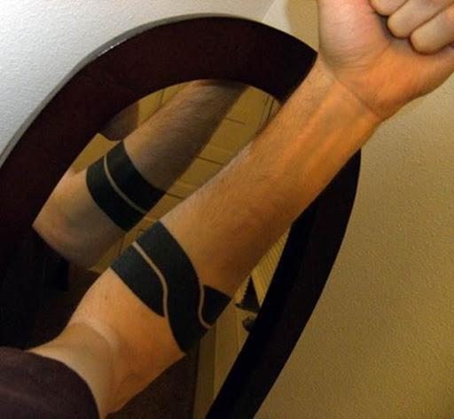 Dois entrelaçar retângulos preto criar a braçadeira descrito logo abaixo do utente cotovelo nesta fotografia.