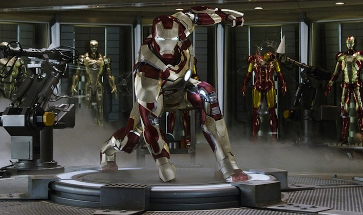 Iron Man in crouched action pose amidst other suits in the armory