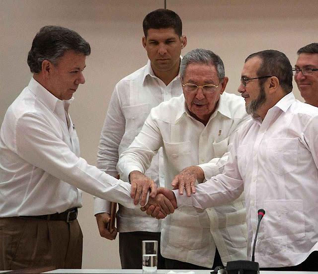 Presidente colombiano cumprimenta líder guerrilheiro das FARC nas conversações de paz em Havana, sob o olhar satisfeito de Raúl Castro.