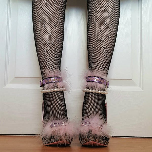 front facing legs in black embellished fishnet tights with black glitter platform shoes with pink feathered heart across toe