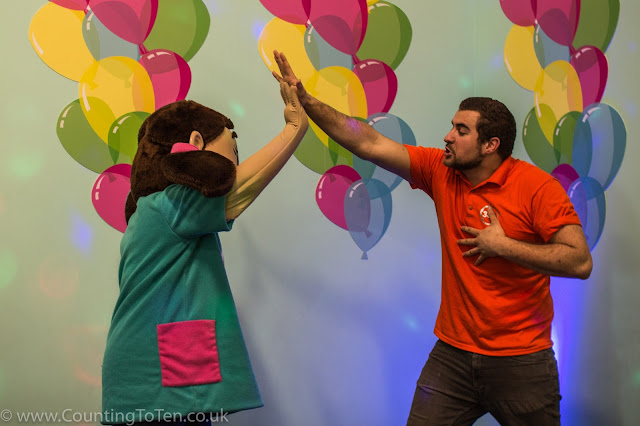 A man in an orange shirt high fiving a character with a foam head