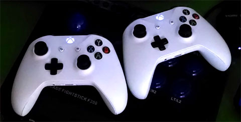 Two white Xbox One controllers.