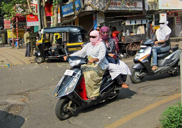 masked women riding a scooter in Pune