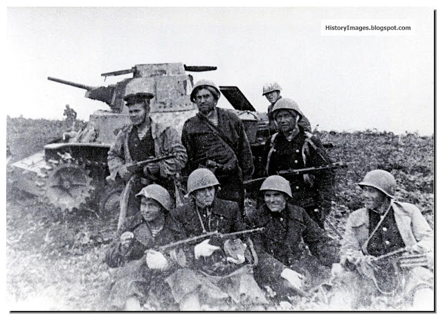 Russian soldiers pose against a destroyed Japanese tank on Shumshu Islands (in the Kuril Islands)