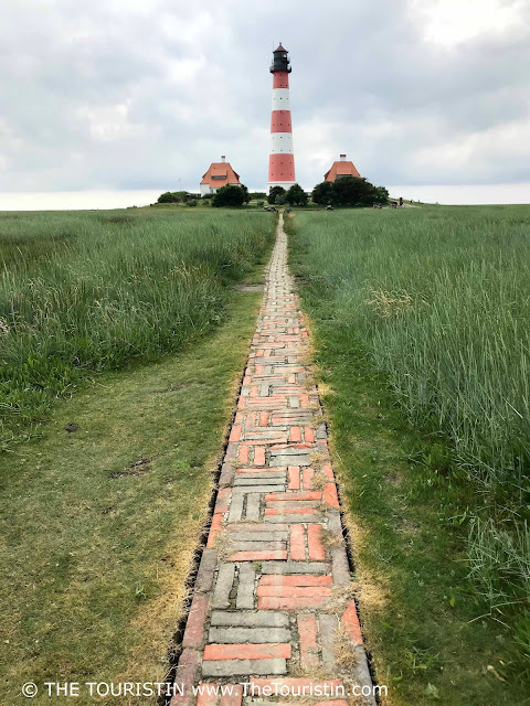 A long and narrow red brick path leading to a red and white lighthouse