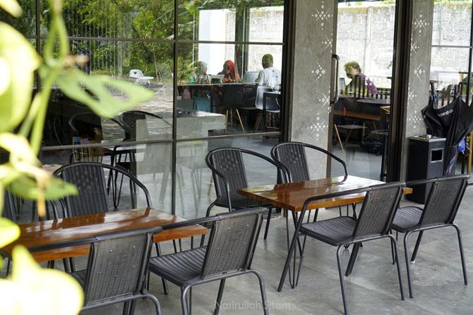 Tatanan kursi di bagian luar kedai kopi untuk perokok