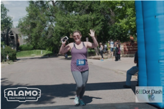 Runner happily crossing the 6 Dot Dash 5k finish line sponsored by Alamo Drafthouse