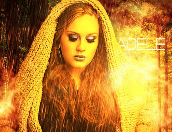 Adele wearing a thick shawl over her head stans in a firey goldish rain