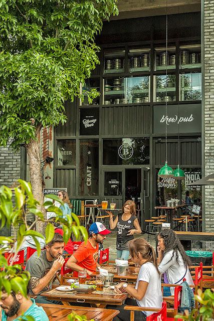 Gente comiendo en mesas a la calle con cerveza.