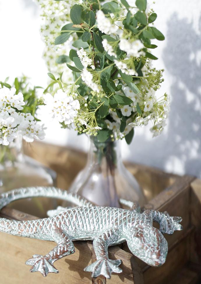 Weiße Blüten in Balsamicoflaschen in Holzschale mit Metallechse im Vordergrund.