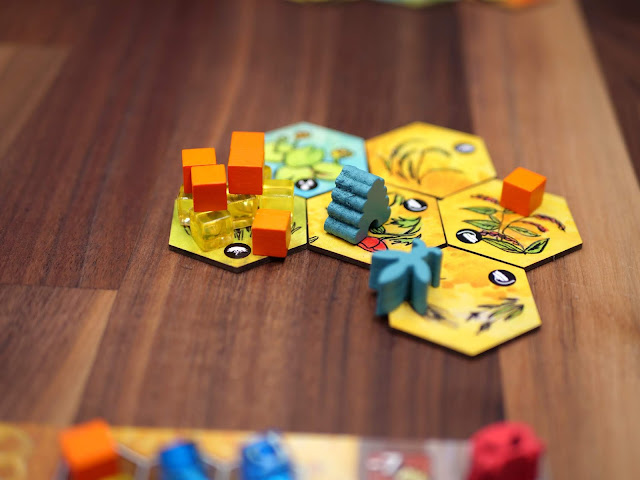 Some hexagonal tokens with clear and solid cubes and a beehive meeple on top