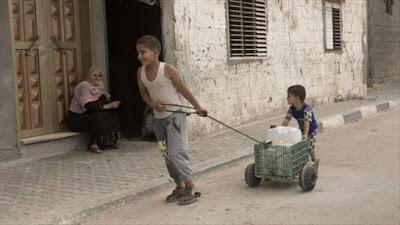 Niño palestino empuja un contenedor de agua.