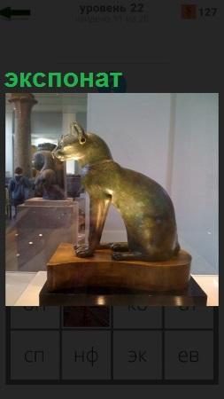 В музее за стеклом стоит экспонат в виде статуи дикой кошки из бронзы