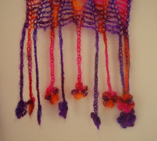 The fringe of the Fantasy Floral scarf is made up of dainty 5-petalled flower motifs at the end of crocheted chains of differing lengths.  Between the body of the scarf and the flowers the chain gets thinner by adjusting the hook sizes downwards. Each purple stripe has a purple chain/flower extending from its end; similarly pink/orange/purple flowers and chain extend from the pink/orange/purple stripe ends.