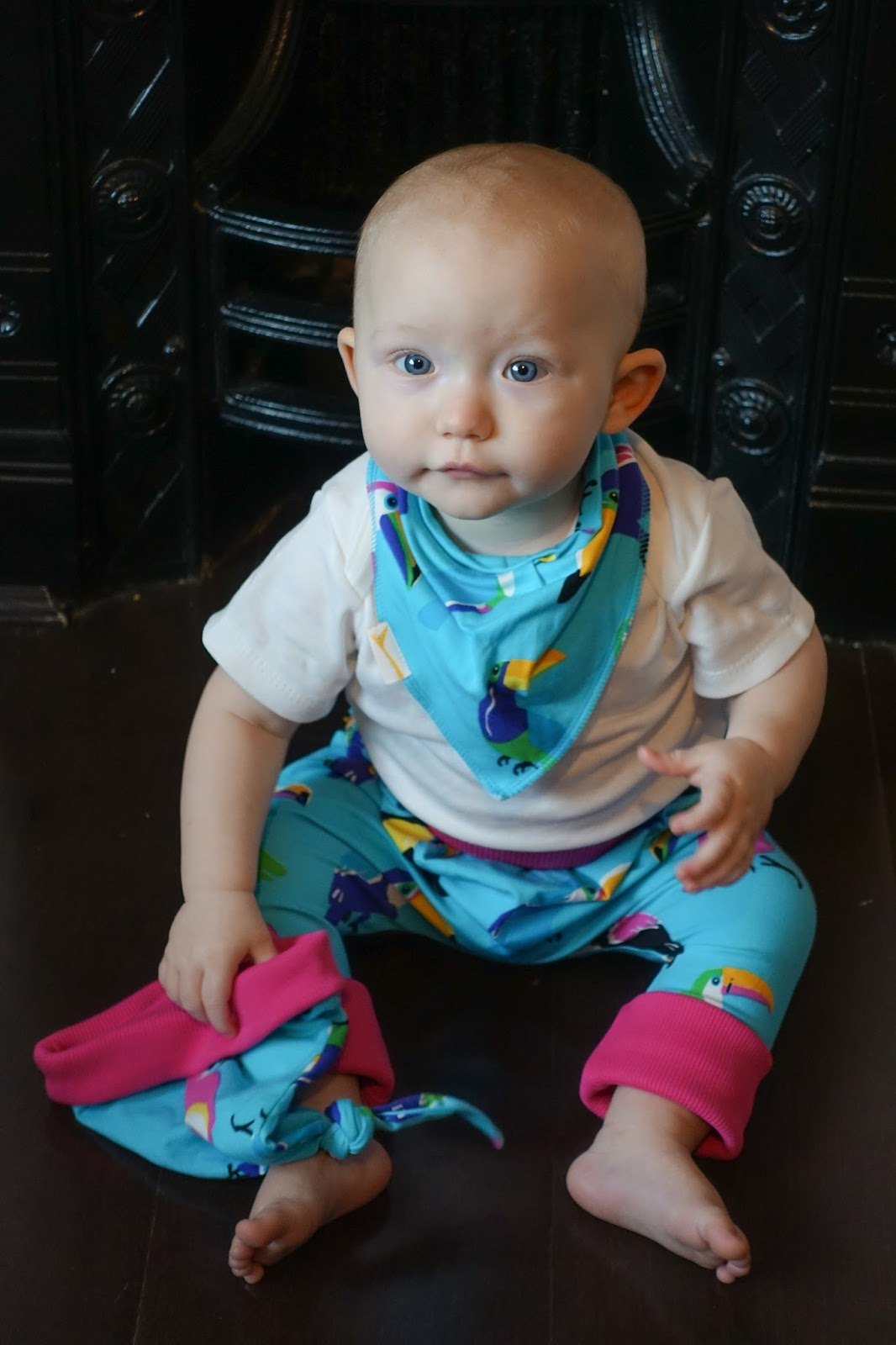 A baby wearing Funky Giraffe Funky Toucan trousers and bib and holding the hat