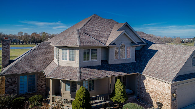 An ugly house that isn't symmetrical at all is photographed from above with a drone
