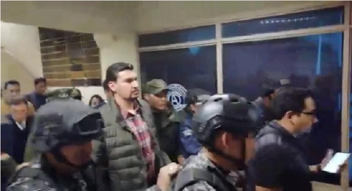 Leyes escoltado por un contingente policial a su salida de la audiencia informativa / RRSS LOS TIEMPOS