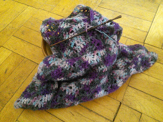 A crochet scarf in a multicolour yarn.  The yarn is purple, with spots of black, pastel blue, and pastel pink.  The scarf is folded up in a wooden yarn bowl, and a wooden crochet hook is on top of the scarf.