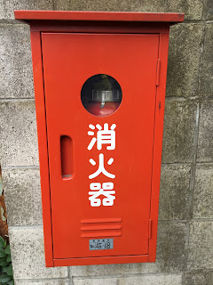 A picture of a fire extinguisher in an orange box on a Tokyo street with the kanji written down the front