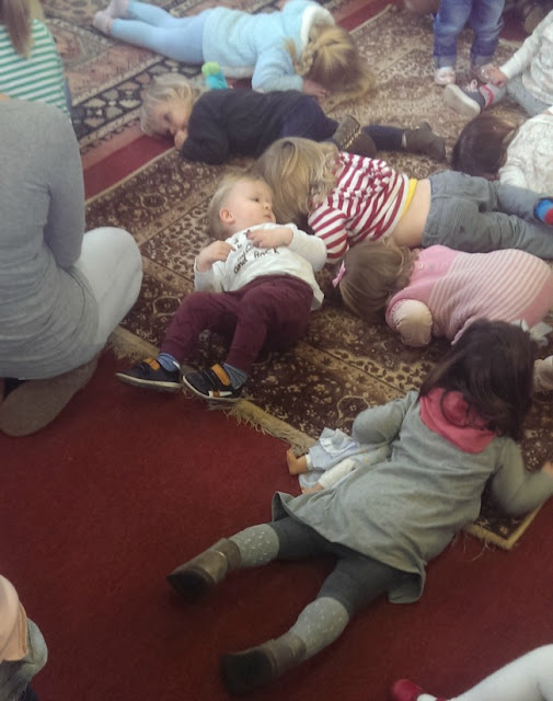 toddlers lying on floor at Tots Club. shhh