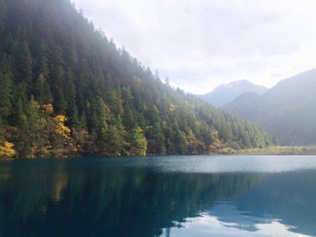 Mặt hồ phẳng lặng, soi bóng rừng cây đổi màu vào mùa thu.