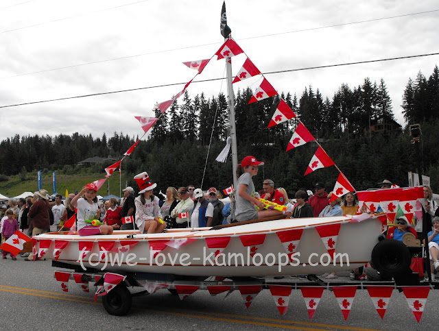 A boat is covered with Canadian flags, passes by as a float in the parade.