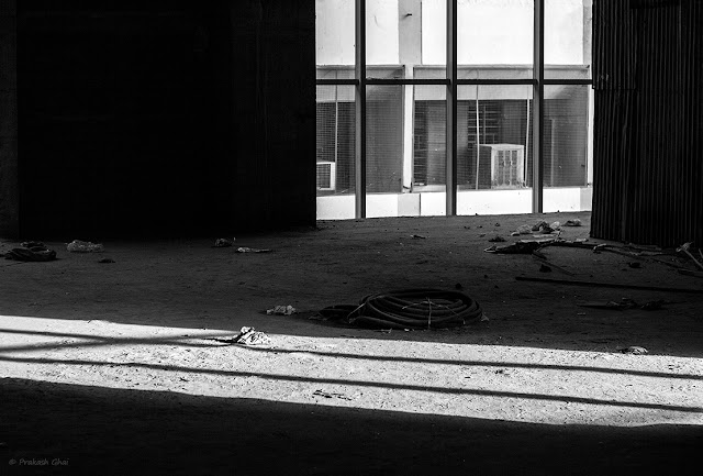 A black and white Minimalist Photo of a window at a building under construction being illuminated by the light coming from outside.