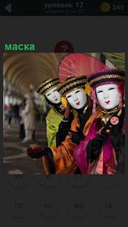 Три женщины стоят в ряд друг за другом в костюмах и масках для маскарада