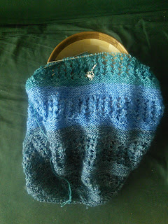 A shawl on a circular needle, laying on top of a wooden yarn bowl. The shawl has alternating stripes of garter stitch and lace, and the yarn is a striping gradient yarn.