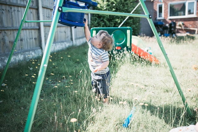 blonde toddler boy standing in a garden and reaching up to touch a blue swing