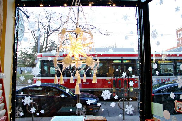 white paper handmade pajaki chandelier hanging in a store window