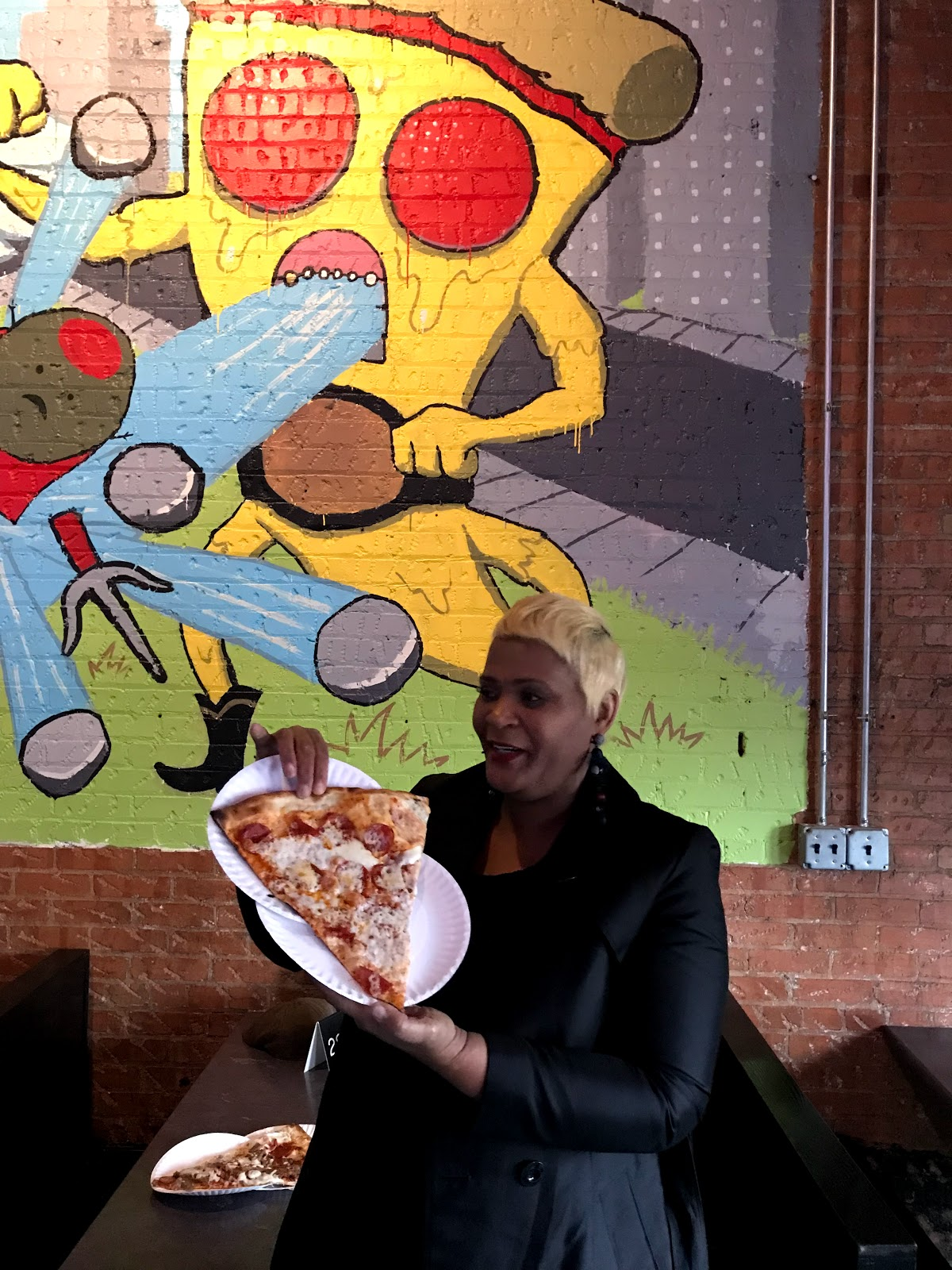 Image: Woman holding large slice of pizza at place in Deep Ellum