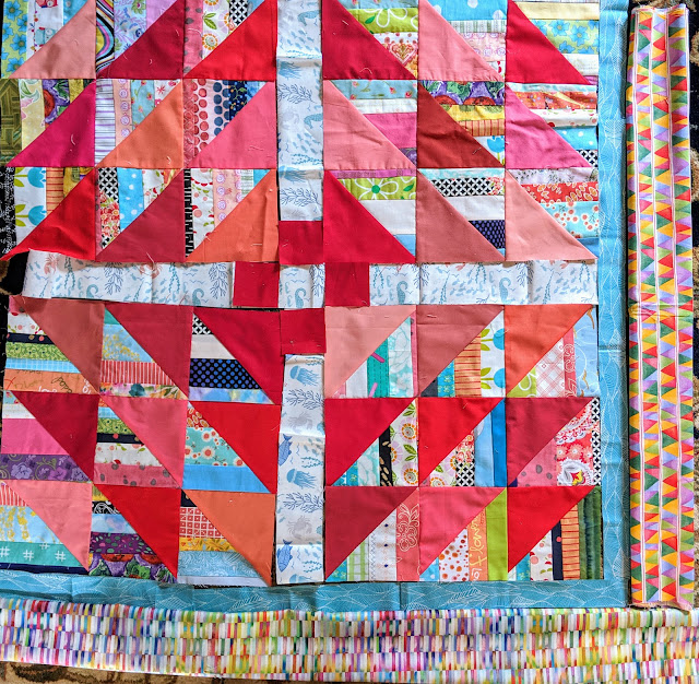 Components of The Square Deal are arranged with a narrow turquoise inner border and two choices for the outer border. Both are multi-colored. One is made printed of small rectangles and the other of small triangles.