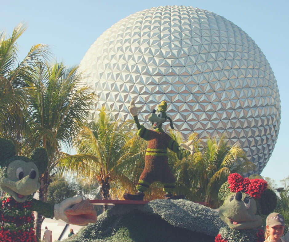 Spaceship Earth at Epcot with mickey mouse and minnie mouse hedges in front of it. Find out the best places to eat in Epcot, one of Walt Disney World theme parks.