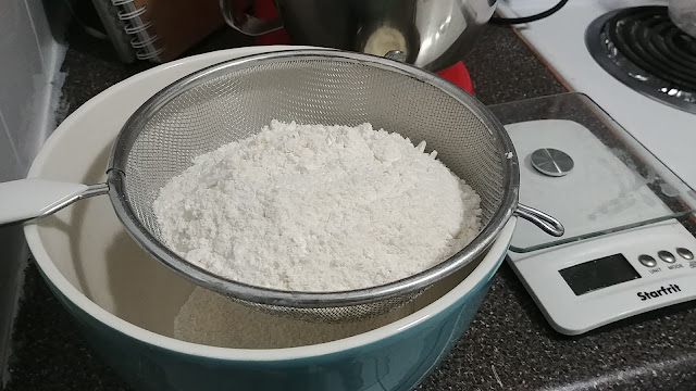 The processed almond meal and icing sugar in a sifter on top of a bowl