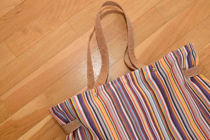 Die Träger-Ausführung der Carrybag, aus Korkstoff und durch Auslässe im Stoff geschlungen, mit 6 Buchschrauben fixiert