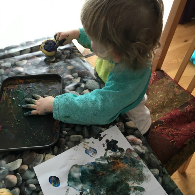 Toddler with hand in paint and finger on potato stamp