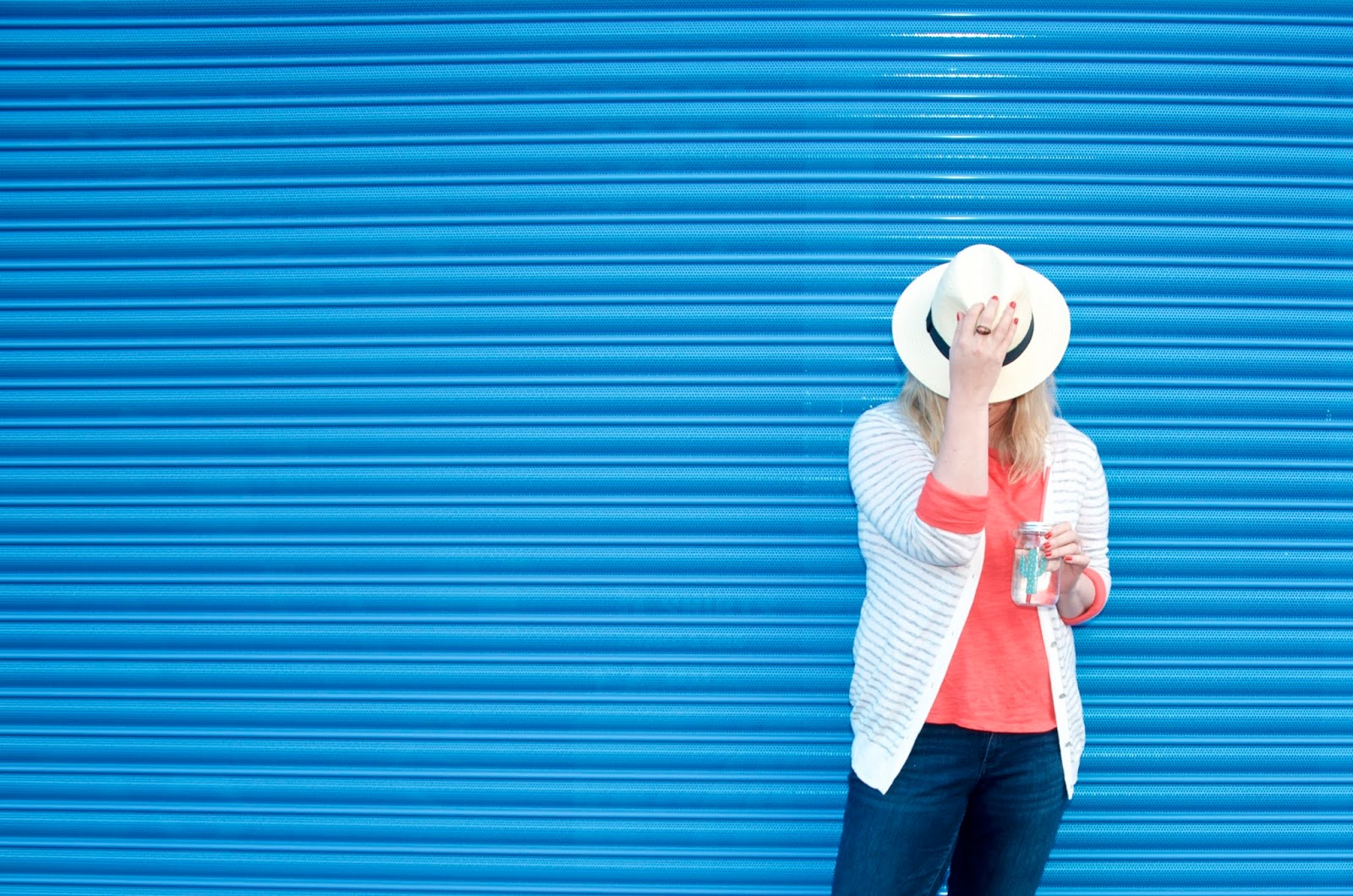 blue wall, panama hat, coral shirt, white cardigan and jeans