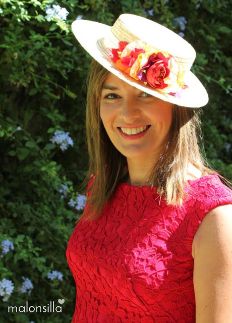 Invitada con canotier de copa baja, cinta blanca y flores en tonos rojos y naranja de marca malonsilla, vestido rojo y pelo suelto