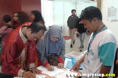 DAFTAR : Para pemgunjung stand kami bisa langsung mengisi form dan transaksi hari itu juga untuk diproses lebih transaparent.  Azman dan istrinya Amuy mendaftar di stand. Photo Mas Bambang