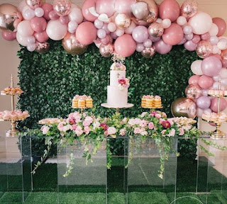 Organic balloon arch, flower centerpiece for cake table, and greenery background for cake table