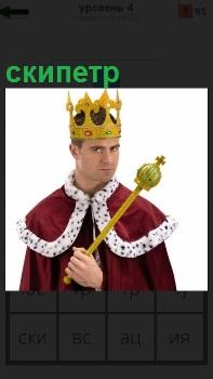 Мужчина в мантии короля с короной на голове и скипетр в руках с серьезным видом