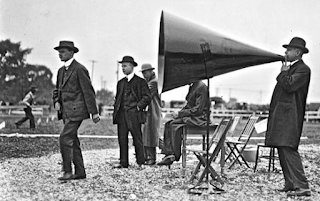 Vintage photo of a man speaking through a huge megaphone, proclaiming how a vintage Chambers stove is carbon friendly