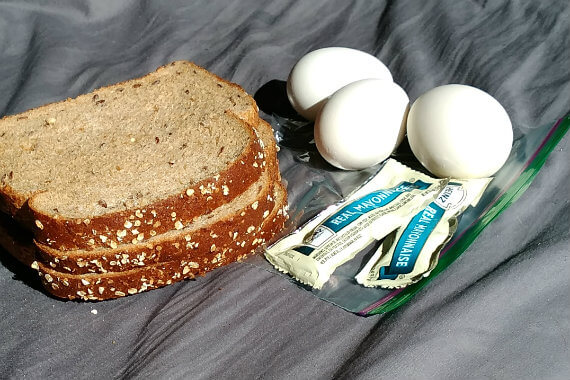 ingredients for egg salad sandwich: bread, boiled eggs, mayonnaise packets, Ziploc