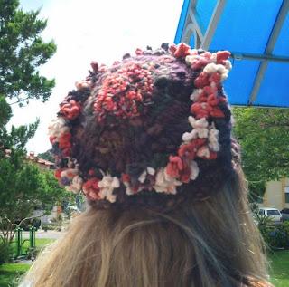 gorro de lã  marrom com enfeitos coloridos na cabeça de uma moça , visto por trás
