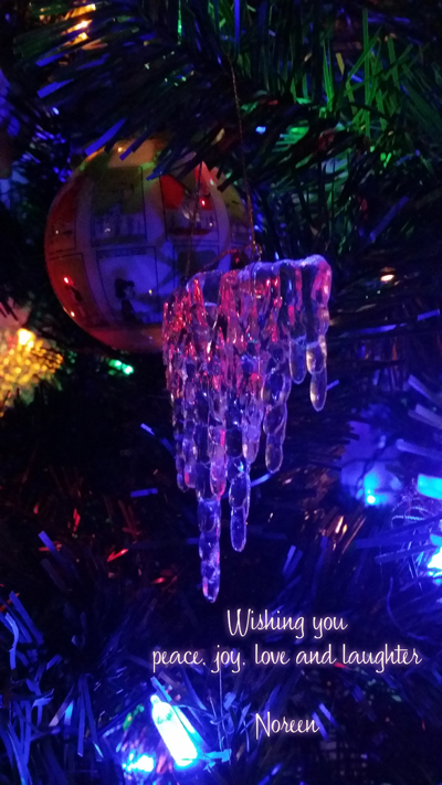 "Icicle ornament hanging from a lit Christmas Tree. ""Wishing you peace, joy, love and laughter.  from Noreen"""