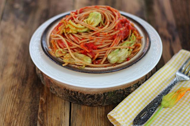 Pełnoziarniste spaghetti z pastą ajvar i kwiatami cukinii.