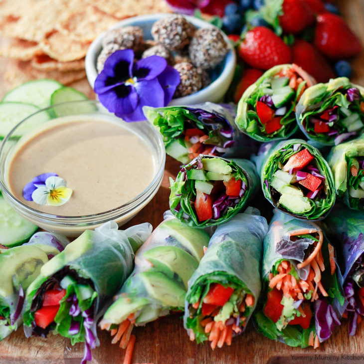 Beautiful vegan spring rolls with avocado, carrots, and bell pepper, and a peanut dipping sauce.