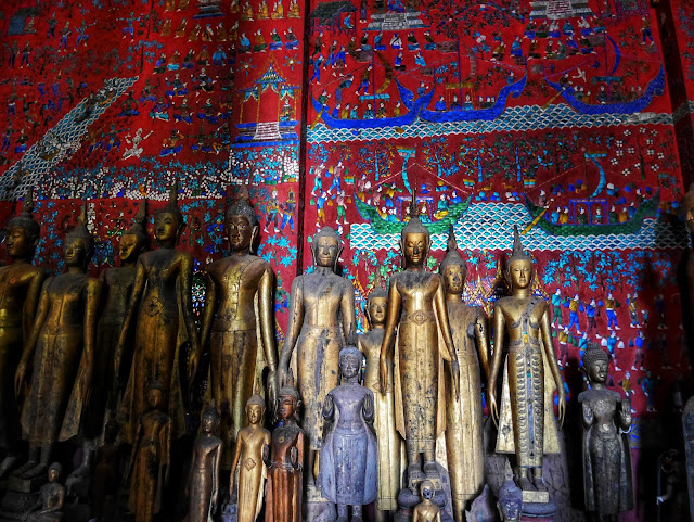 bronze Buddha statues stand before a red wall covered in intricate glass tile mosaics depicting scenes from Lao life
