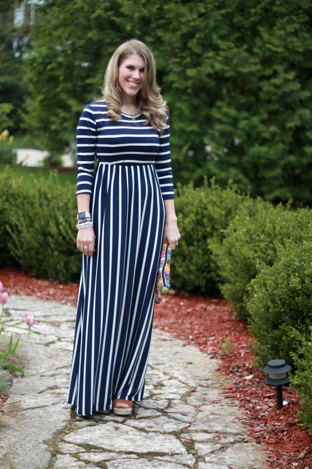 navy blue striped maxi dress, pom pom clutch, cognac wedges, pink leather earrings